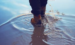 Un hombre en zapatos impermeables cruza la charca imagenes de archivo