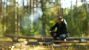 Un hombre enciende un fuego en el bosque en la naturaleza, reconstrucción al aire libre, borrosa, fondo, acampando almacen de metraje de vídeo