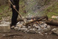 Un hombre enciende un fuego en el forestMan pone la rama seca en hoguera El turista enciende el fuego Reconstrucción al aire libr foto de archivo libre de regalías