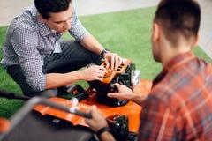 Un hombre enciende un motor del cortacésped fotografía de archivo libre de regalías