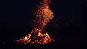 Un hombre endereza los carbones ardientes de las bifurcaciones en el fuego chispas de un fuego contra el cielo oscuro metrajes