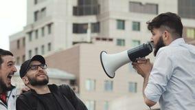 Un hombre enojado con una barba grita en alta voz en la gente en un megáfono metrajes