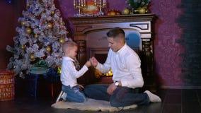 Un hombre enseña su hijo a un gesto complicado del saludo en una celebración de la Navidad metrajes