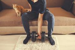 Un hombre entra para los deportes en casa con pesas de gimnasia con un gato foto de archivo libre de regalías