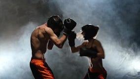 A un hombre entrena al boxeador de la muchacha Entrenamiento del boxeo en el anillo Cámara lenta Fume el fondo almacen de video