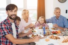 Un hombre es de presentación y de mirada de la cámara en el fondo de una familia que se siente en una tabla festiva para la acció Fotos de archivo libres de regalías