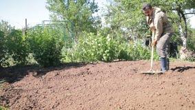Un hombre es granjero en las botas de goma en el área suburbana, un huerto, con la ayuda de una azada reduciendo el preparin de l almacen de video