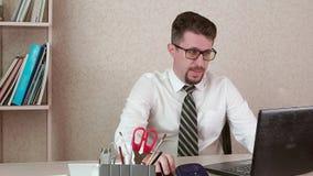 Un hombre es oficinista con un funcionamiento de la barba y de vidrios en un ordenador portátil almacen de video