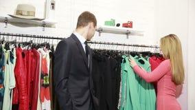 Un hombre espera a su mujer elige un vestido en una tienda nervioso y toma la primera ropa disponible almacen de video