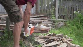 Un hombre está aserrando la madera con una sierra eléctrica metrajes