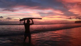 Un hombre está caminando con una resaca en sus manos a través de la orilla de mar almacen de video