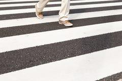 Un hombre está caminando en el paso de cebra Imagen de archivo