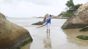 Un hombre está circundando a una muchacha en sus brazos en una playa arenosa del mar Un par de amantes remolina en la cámara lent almacen de metraje de vídeo