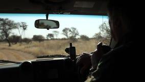 Un hombre está conduciendo un coche en la sabana almacen de metraje de vídeo