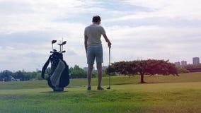Un hombre está consiguiendo listo para comenzar a jugar a golf almacen de metraje de vídeo