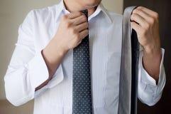 Un hombre está eligiendo una corbata Foto de archivo libre de regalías