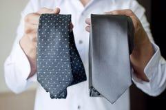 Un hombre está eligiendo una corbata Fotografía de archivo
