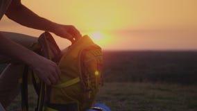 Un hombre está embalando su mochila en la puesta del sol Preparación para un viaje o el emigrar almacen de video