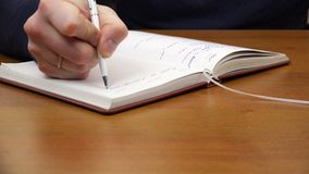 Un hombre está escribiendo en un cuaderno metrajes