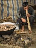 Un hombre está fumando un tubo grande detrás de una cacerola grande con la carne en el mercado de la mañana de Bac Ha Foto de archivo