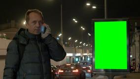 Un hombre está hablando en el teléfono en la noche en la ciudad Un smartphone es los medios de la comunicación Contra el fondo