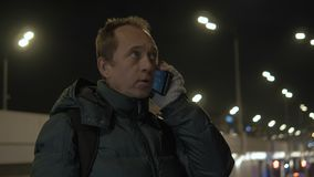 Un hombre está hablando en el teléfono en la noche en la ciudad SMS de marca, primer metrajes