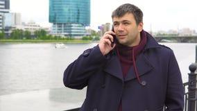 Un hombre está hablando en un teléfono móvil contra el contexto de un paisaje urbano metrajes