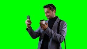 Un hombre está hablando en un teléfono móvil en modo de vídeo almacen de metraje de vídeo