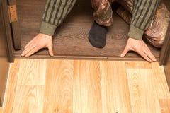Un hombre está haciendo un umbral en el piso foto de archivo