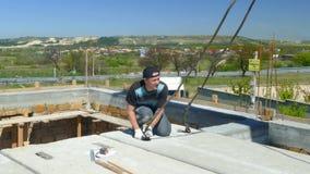 Un hombre está instalando un bloque de cemento en el tejado del edificio almacen de metraje de vídeo
