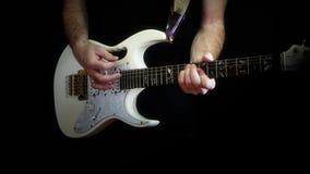 Un hombre está jugando en una guitarra eléctrica blanca en un fondo negro almacen de metraje de vídeo