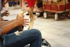 Un hombre está jugando la pandereta en el parque Foto de archivo