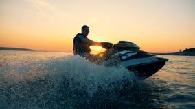 Un hombre está montando un jet-esquí a lo largo de la costa costa durante puesta del sol almacen de video
