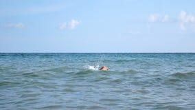 Un hombre está nadando en el mar almacen de video