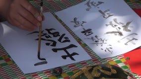 Un hombre está practicando caligrafía usando una pluma del cepillo en su tiempo libre almacen de video