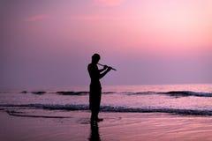 Un hombre está practicando tocando la flauta en el abedul en la puesta del sol Goa, la India 16 01 2018 Imagen de archivo