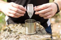 Un hombre está preparando el café en una taza imágenes de archivo libres de regalías
