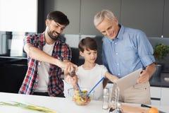 Un hombre está preparando una ensalada El muchacho y el viejo hombre se colocan de lado a lado y mirada en algo en la tableta del Fotografía de archivo