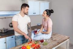 Un hombre está preparando una ensalada para su muchacha querida mientras que ella bebe un vino tinto delicioso Ella lo ama mucho imagen de archivo libre de regalías