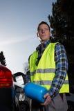 Un hombre está reaprovisionando su coche de combustible en la calle Fotos de archivo