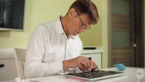 Un hombre está reparando un ordenador portátil El concepto de reparación del ordenador Ciérrese para arriba de la placa madre del almacen de metraje de vídeo