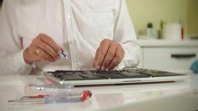Un hombre está reparando un ordenador portátil El concepto de reparación del ordenador Ciérrese para arriba de la placa madre del almacen de video