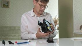 Un hombre está reparando una unidad de café-fabricación de una máquina del café, taller de reparaciones de los fabricantes de caf almacen de video