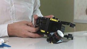 Un hombre está reparando una unidad de café-fabricación de una máquina del café, taller de reparaciones de los fabricantes de caf almacen de metraje de vídeo