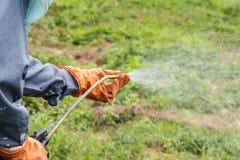 Un hombre está rociando el herbicida Imagen de archivo libre de regalías
