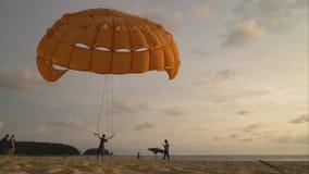 Un hombre está sosteniendo un paracaídas en la dirección del viento en la playa Timelapse almacen de video