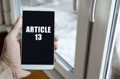 Un hombre está sosteniendo un smartphone con la inscripción del artículo 13 imagen de archivo
