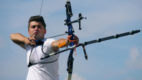 Un hombre está tirando de su arco compuesto Tiroteo con un arco y las flechas almacen de video
