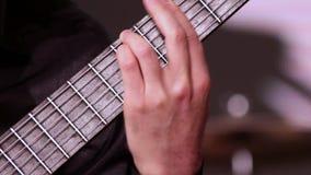 Un hombre está tocando la guitarra Cantidad en un tema musical Un primer de la mano izquierda que pone los acordes en el fretboar metrajes