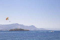 Un hombre está volando en un ala flexible sobre el mar, siguiendo un barco t Fotografía de archivo